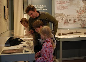 Family gather around an exhibition inside the Old State House Museum