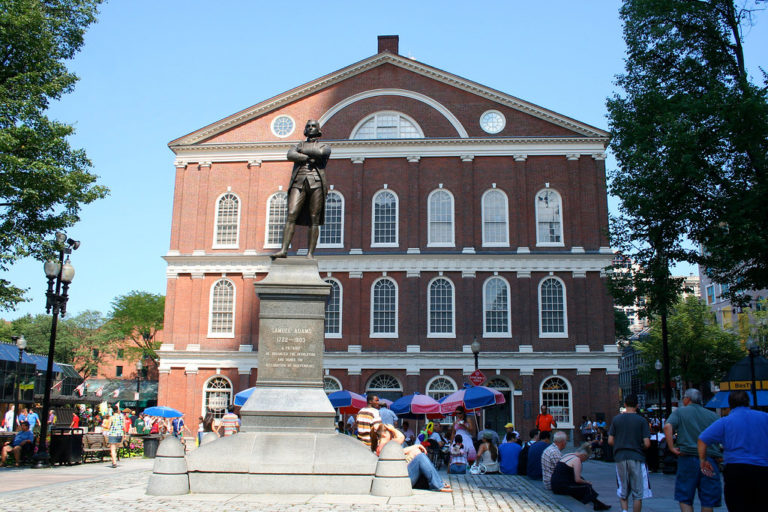 People walking by the Sam Adams statue with Faneuil Hall in the background