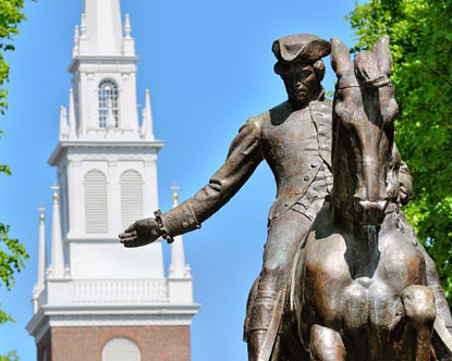 Image of the Old North Church in the background of a statue of a man in a horse