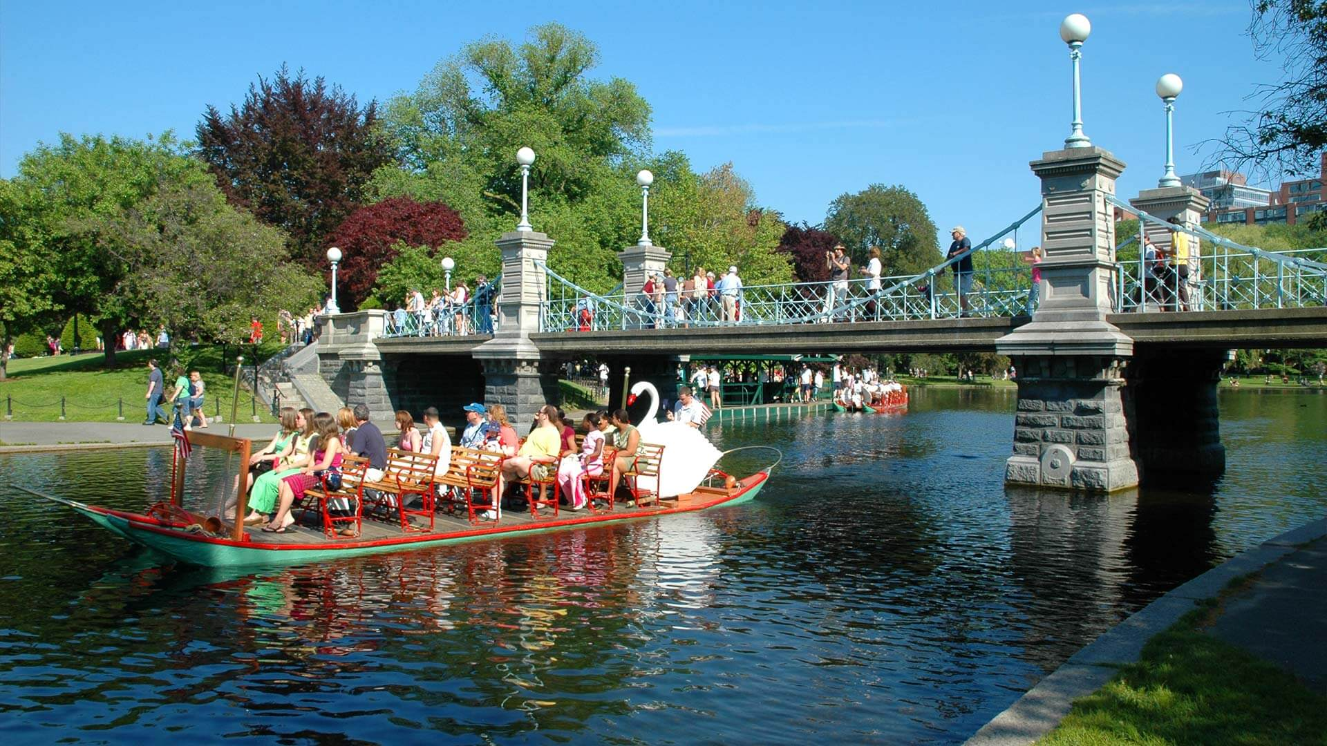 People enjoying the Swan Boats ride in Boston Public Garden on a sunny day
