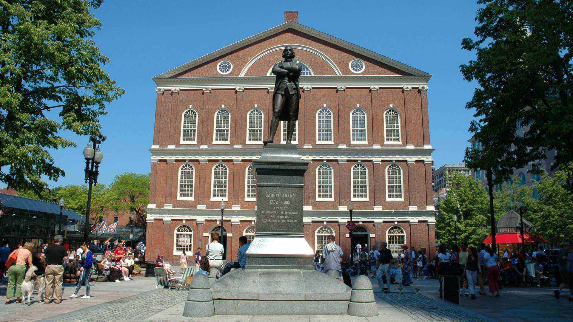 Front view of Samuel Adams statue with Faneuil Hall in the background in Boston