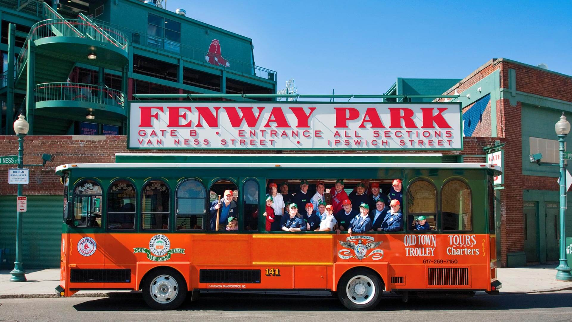 Smiling tourist waving inside an Old Town Trolley that's passing by Fenway Park in Boston