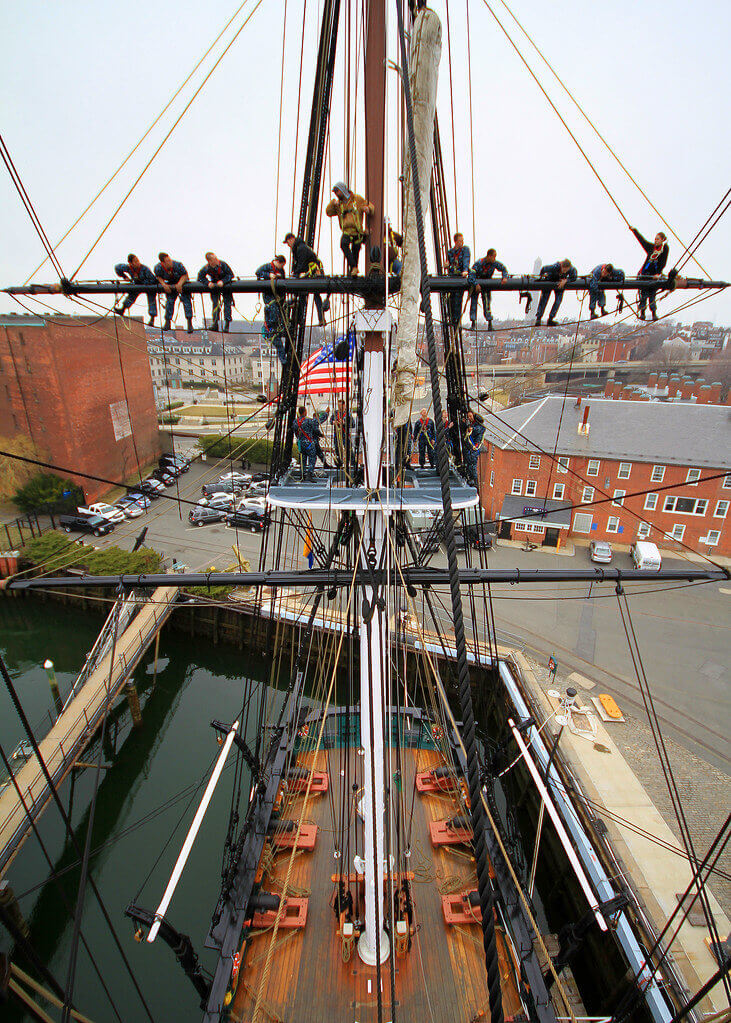 Men hanging out on the mast of a ship