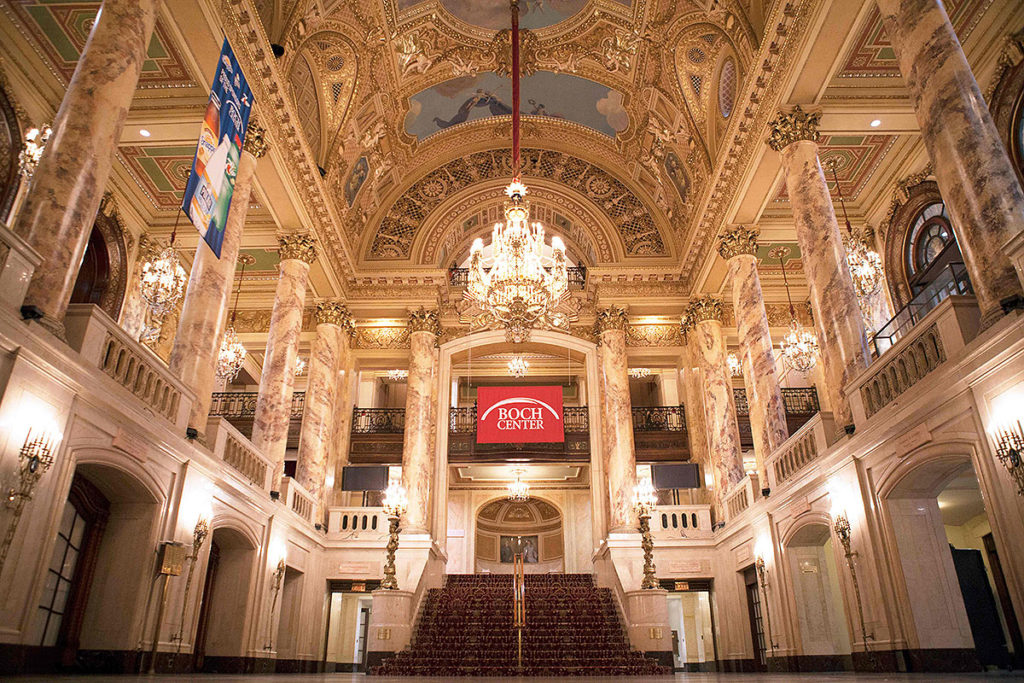 picture of boch center lobby featuring two floors, a set of carpeted stars, ornate walls and ceiling, a hanging crystal chandelier, and columns on second floor this winter season