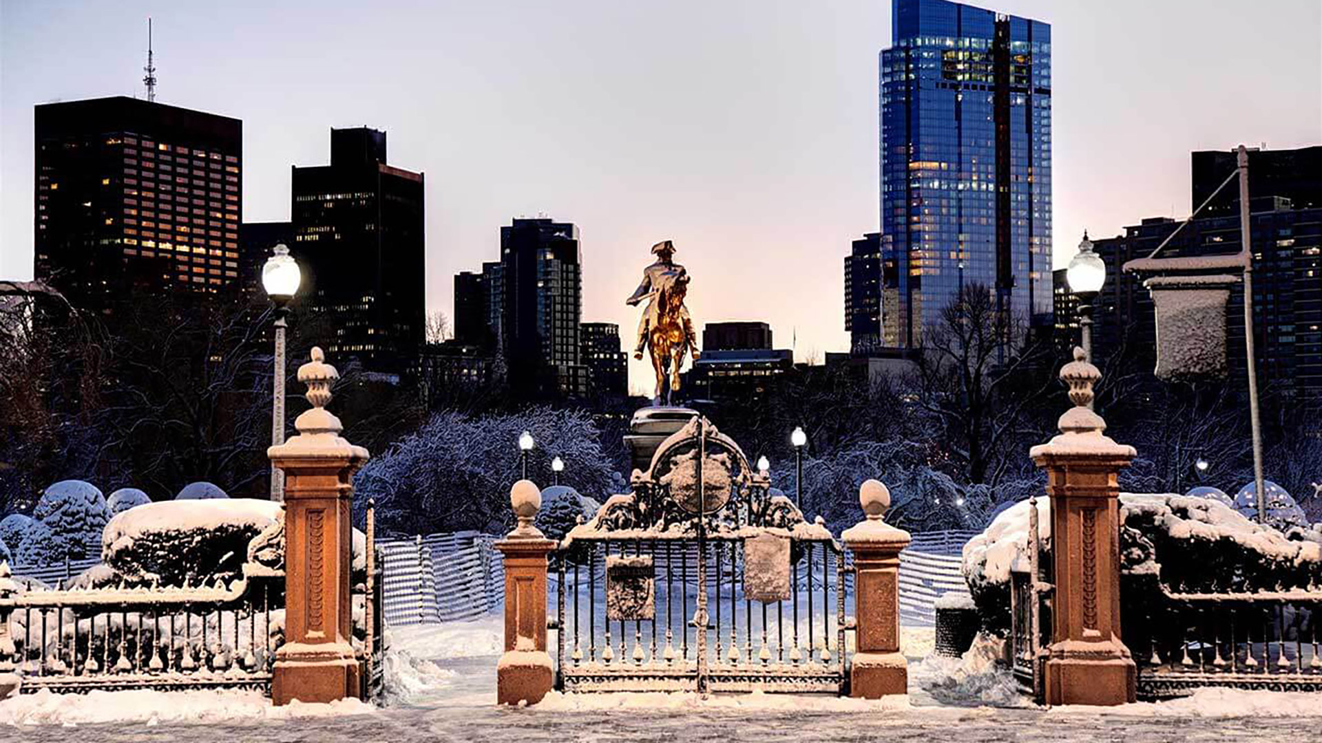 Winter scene at Boston Public Garden featuring gates, fence and trees covered in snow and in the background, a statue of George Washington riding on a horse and the city skyline in the back