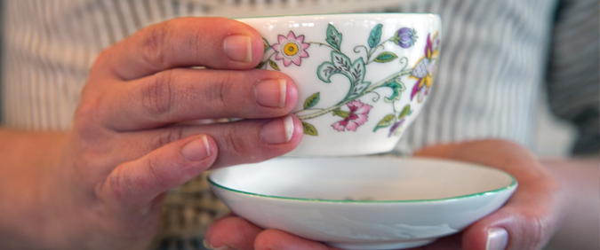 Close-up photo of someone's hand holding a tea cup